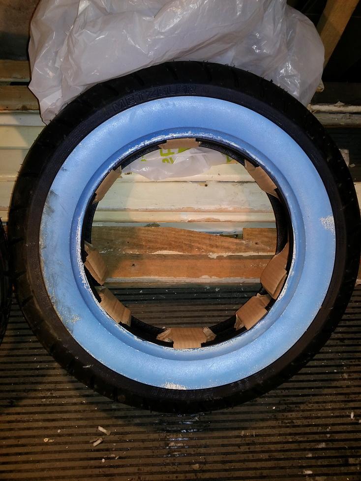 Заднее колесо, будет с белой полосой сбоку, которая для транспотировки покрыта синей зажитной плёнкой.