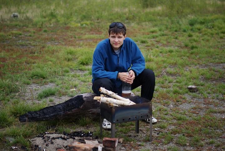 Саня в восторге от отдыха, разжигает мангал сырыми дровами